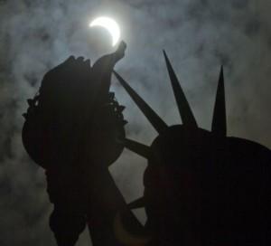 Gedeeltelijke zonsverduistering bij het  Vrijheidsbeeld, 21 augustus (bron: AP Photo/Seth Wenig).